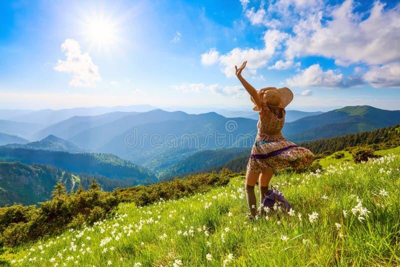 在山的草坪使礼服的,长袜行家女孩环境美化,并且草帽停留观看与云彩的天空 免版税库存照片