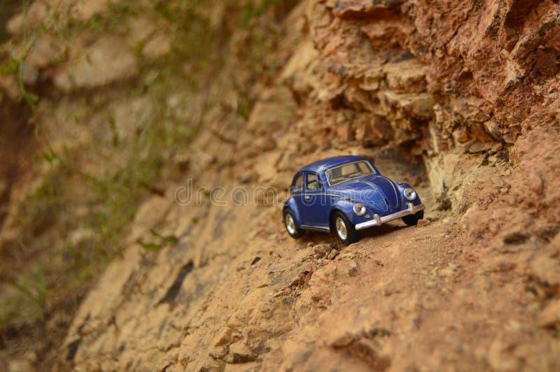在山的蓝色玩具汽车 免版税库存图片