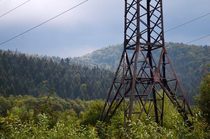 在山的输电线支持在多云天气 库存照片