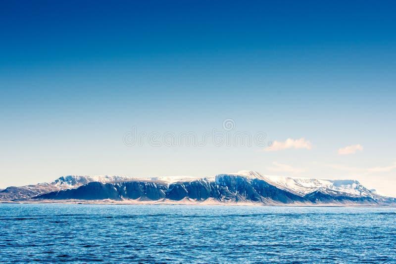 在山的雪在蓝色海洋 免版税图库摄影