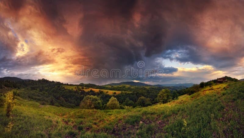 在山的雷暴 与迷人风雨如磐的天空、暴风云、晴朗的谷和小农村H的全景夏天风景 库存照片