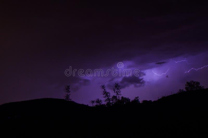 在山的雷电与紫色天空 免版税库存图片