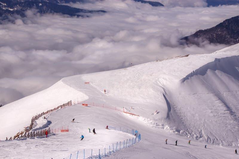 在山的滑雪足迹在云彩上 库存照片