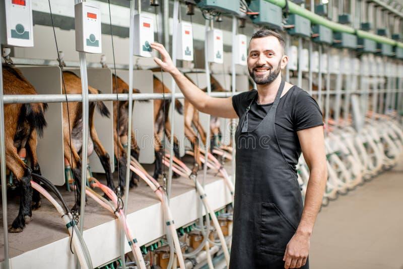在山羊农场的人运行的挤奶机 免版税库存图片