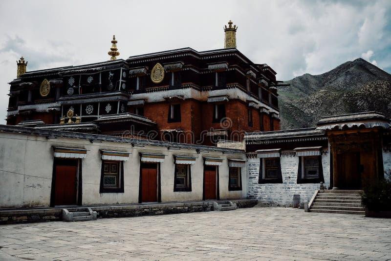 在山脉峰顶前面的西藏佛教寺庙大厦 图库摄影
