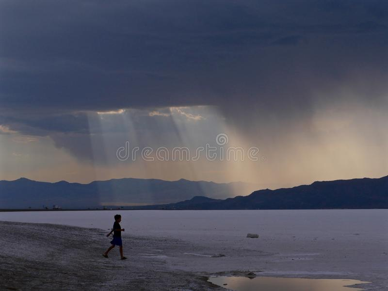 在山脉,跑往邦纳维尔盐舱内甲板的小男孩的黑暗的风雨如磐的天空 库存图片