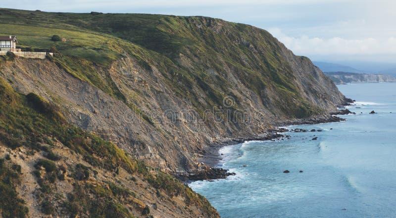 在山自然海岸风景的日落 在背景剧烈的天空,云彩,海海洋的绿色山谷 全景天际 库存图片