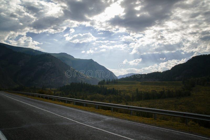 在山谷和暴风云的路在黑暗的天空 免版税库存照片