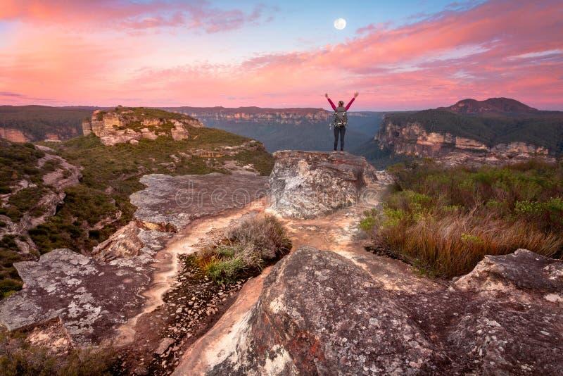 在山顶岩石日出谷壁架视图的妇女身分  免版税库存照片