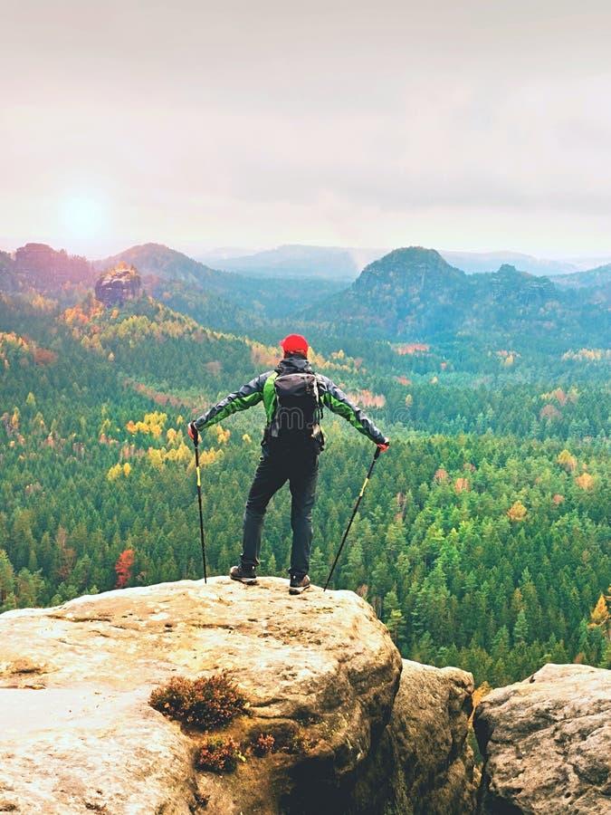 在山顶的旅游指南与杆在手中和重的背包 远足者绿色jakcet nad红色盖帽 免版税库存图片