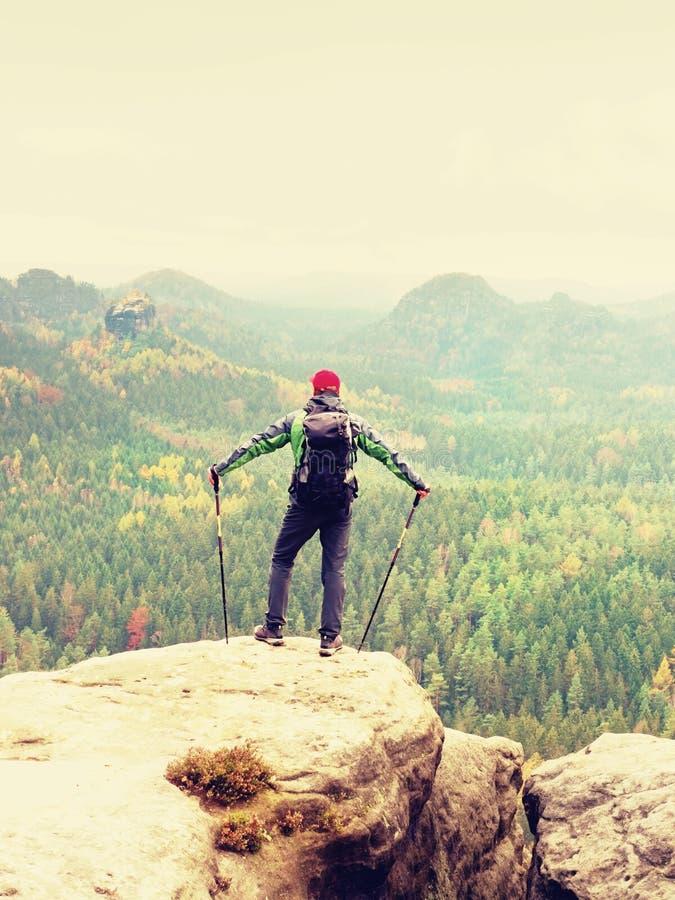 在山顶的旅游指南与杆在手中和重的背包 远足者绿色jakcet nad红色盖帽 图库摄影