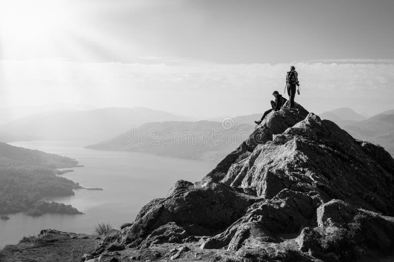 在山顶部的女性远足者享受谷视图的 免版税库存图片