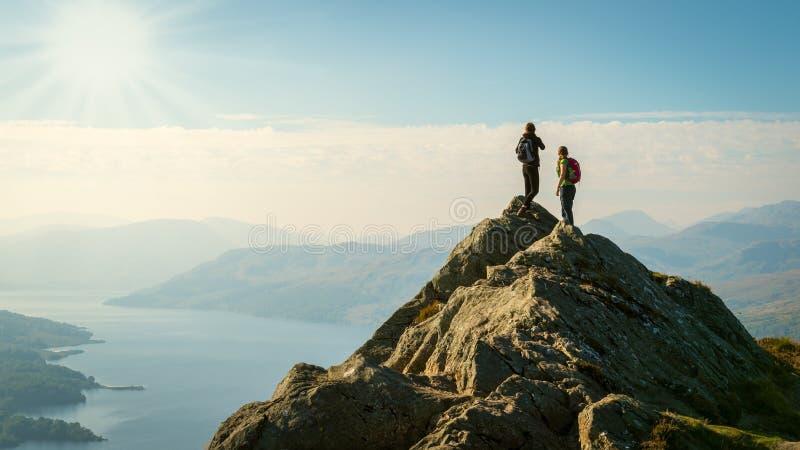 在山顶部的女性远足者享受谷视图的 免版税图库摄影