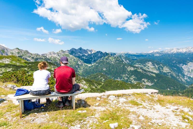 在山顶部的年轻夫妇看对远的小山 斯洛文尼亚山沃热尔,特里格拉夫峰和在Bohinj湖附近 免版税库存图片
