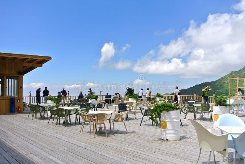 在山顶部的户外咖啡馆与游人 库存照片
