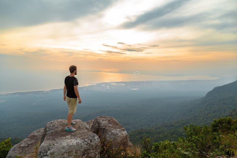 在山顶部的男性远足者享受谷视图的 图库摄影