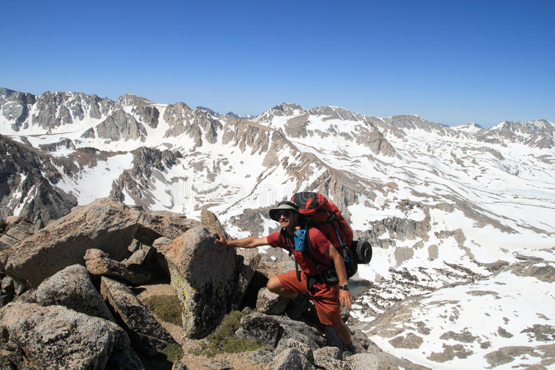 在山顶附近的背包徒步旅行者 库存图片