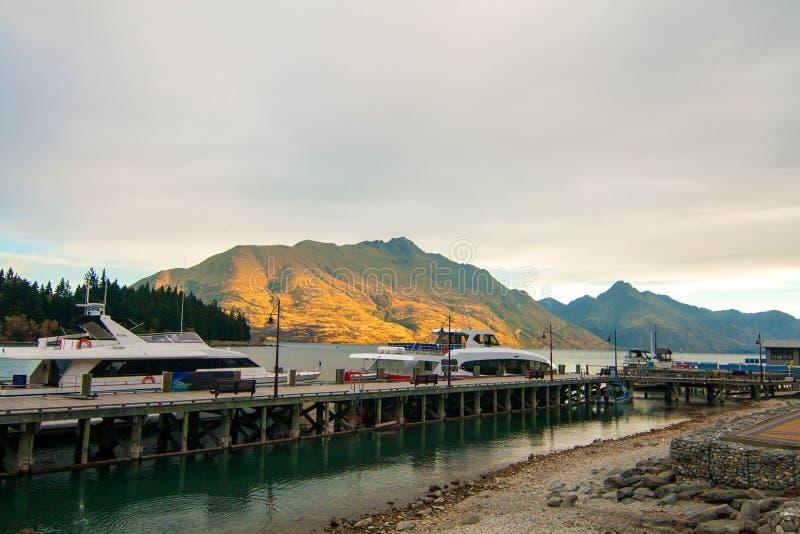 在山,靠码头在湖Wakatipu,昆斯敦码头的豪华小船的美好的金黄日落光 免版税库存照片