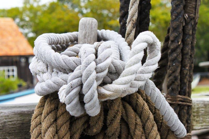 在岗位附近和白色结辨的绳索被栓的布朗在小游艇船坞-选择聚焦有bokeh背景 免版税库存图片