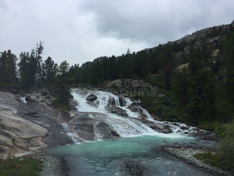 在岩石中的Ioldo-Ayry瀑布 蓝色森林瀑布 阿尔泰山,西伯利亚,俄罗斯 库存图片