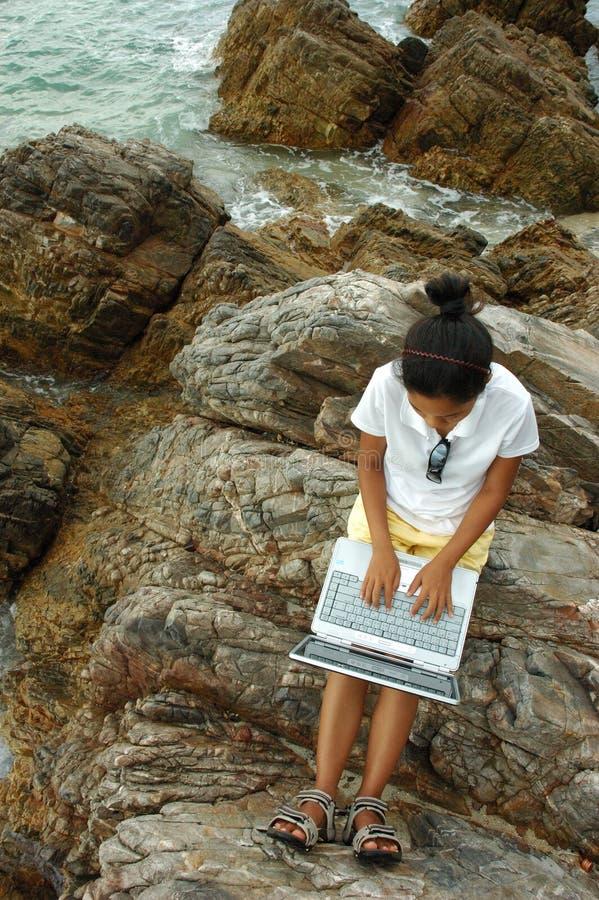 在岩石之外的女孩膝上型计算机使用 免版税图库摄影