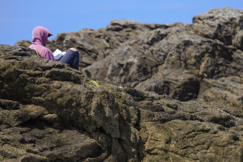 在岩石之间的男孩读书 免版税库存照片