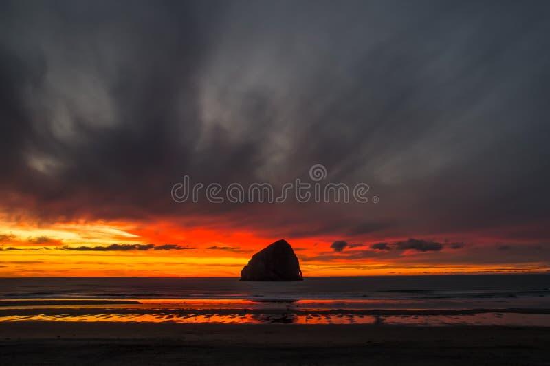 在岩石后的日落在海角Kiwanda的黑暗的云彩下 免版税库存照片