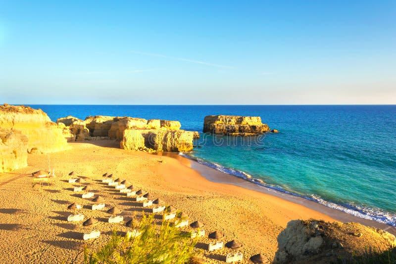 在岩石和峭壁中的美丽的沙滩与在阿尔布费拉附近的sunbeds在阿尔加威 图库摄影