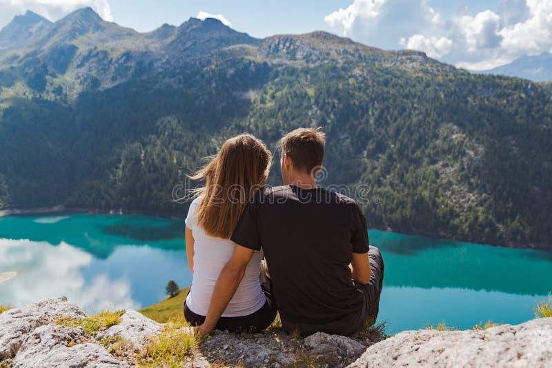 在岩石和敬佩美丽的景色在爱的年轻夫妇供以座位的在瑞士阿尔卑斯 免版税库存图片