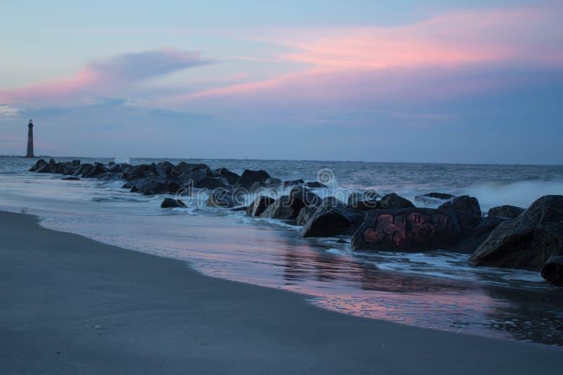 在岩石和灯塔的日落用跑在海滩的水 库存照片