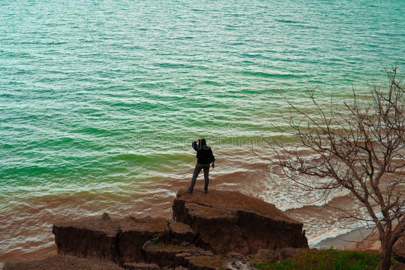 在岩石和看海的上面的年轻女人身分 免版税库存图片