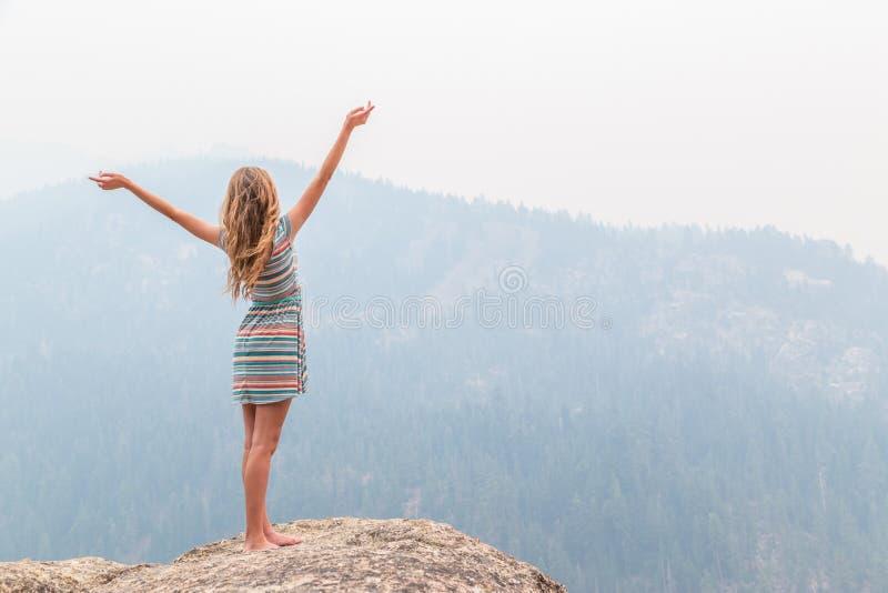 在岩石土坎顶部的十几岁的女孩 免版税库存图片