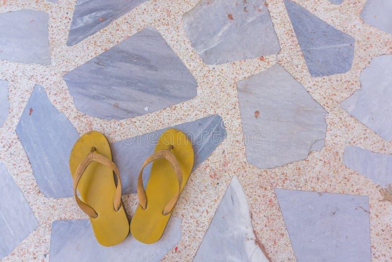 在岩石地板上的黄色凉鞋 免版税库存照片