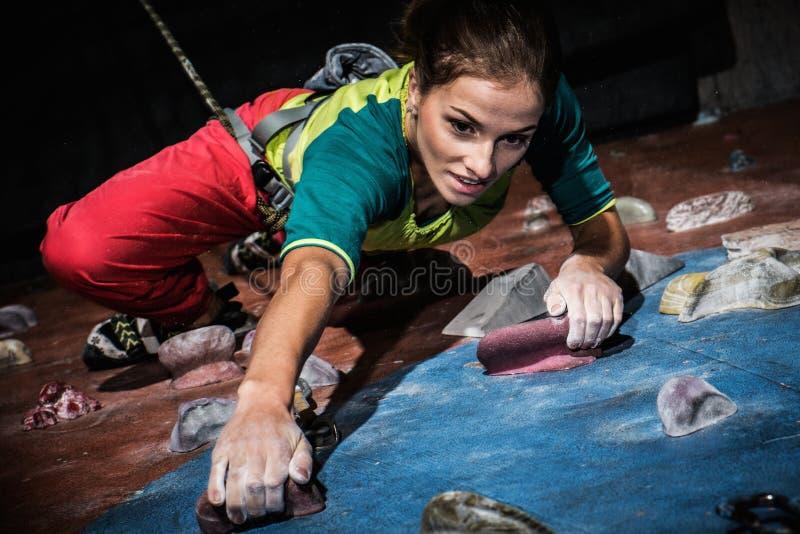 在岩石墙壁上的妇女实践的攀岩 免版税库存图片