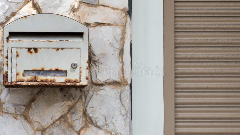 在岩石墙壁上的老邮箱 库存照片