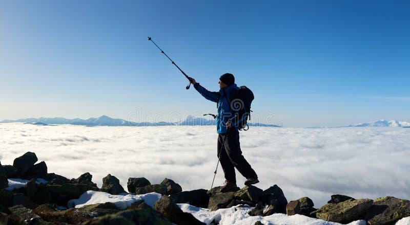 在岩石小山上面的徒步旅行者在谷背景的与白色云彩、多雪的山和天空蔚蓝的 免版税库存照片