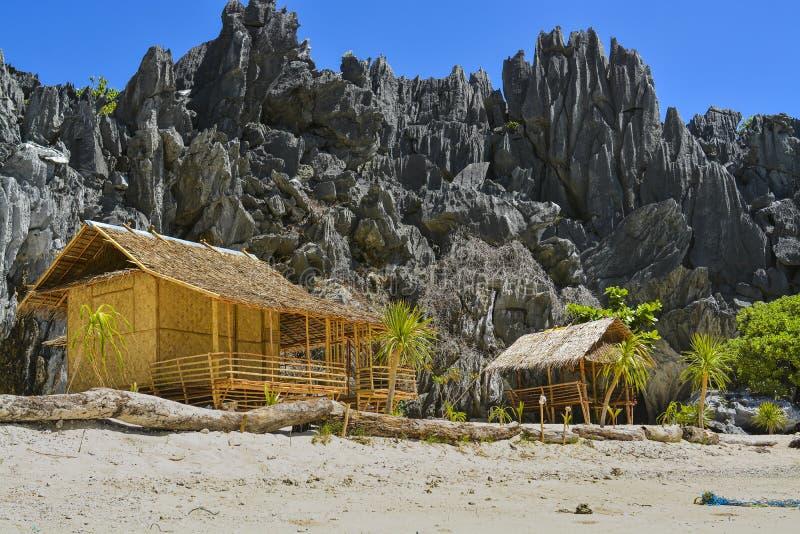 在岩石山前面的木房子 议院在海滩建造 前往菲律宾 库存照片