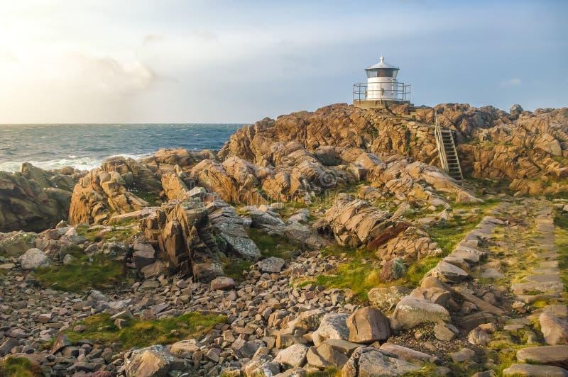 在岩石岸的灯塔在日落期间 免版税库存照片
