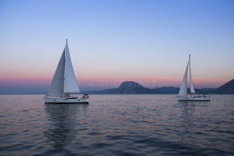 在岩石岸附近的帆船在惊人的日落以后 旅行 免版税库存图片