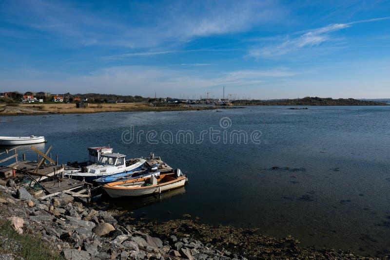 在岩石岸靠码头的小船 免版税图库摄影