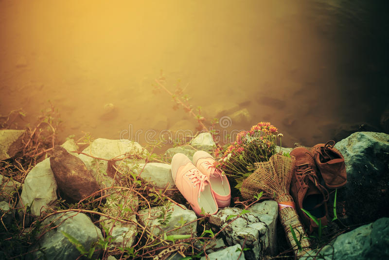 在岩石投入的夫妇鞋子在湖附近 概念亲吻妇女的爱人 免版税库存照片