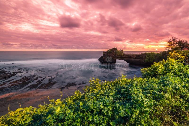 在岩石海岸普拉巴图Bolong,Tanah全部寺庙,巴厘岛,印度尼西亚的五颜六色的日落 免版税图库摄影