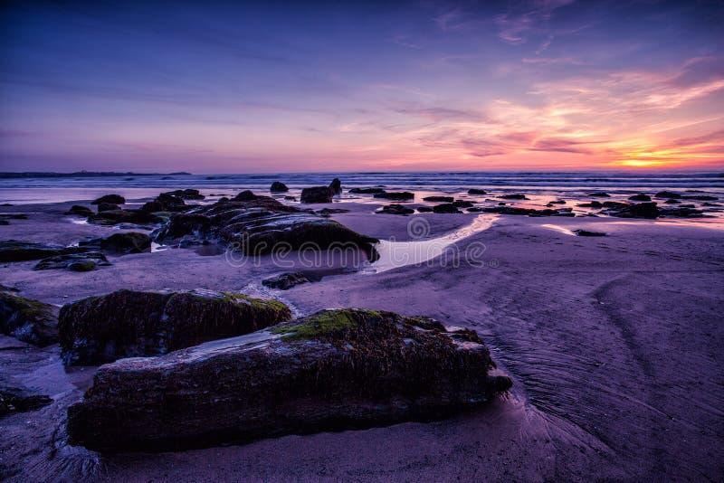 在岩石海岸海滩的紫色天空日落 免版税库存图片