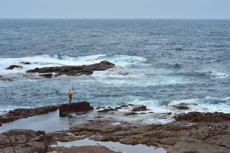 在岩石海岸的岩石渔 图库摄影