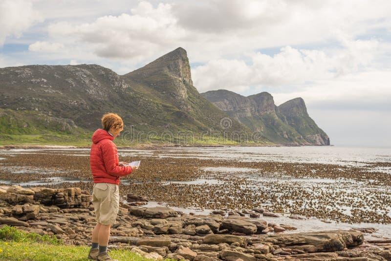 在岩石海岸线的旅游读书地图在开普角,桌山附近国家公园,南非 冬天季节,多云和 图库摄影