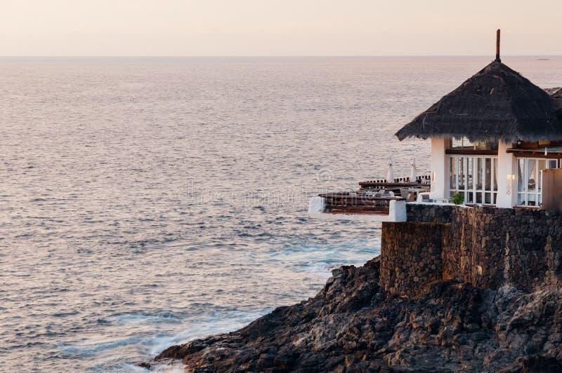 在岩石海岸边缘的餐馆大阳台 免版税库存图片