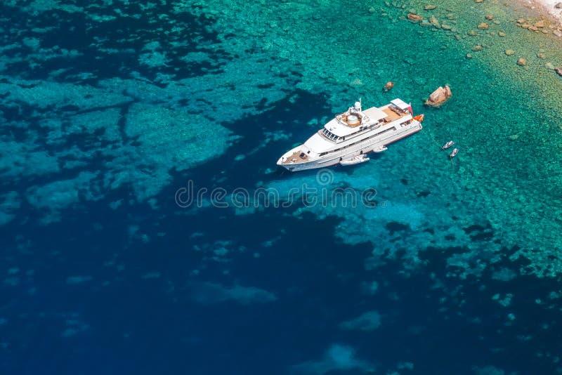 在岩石海岸附近的豪华白色游艇 免版税库存照片
