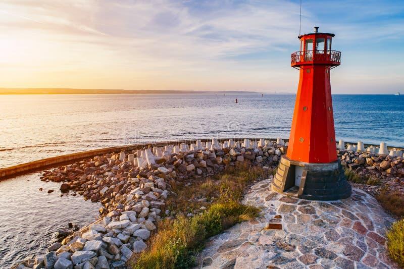 在岩石海滨的红色灯塔 免版税库存照片