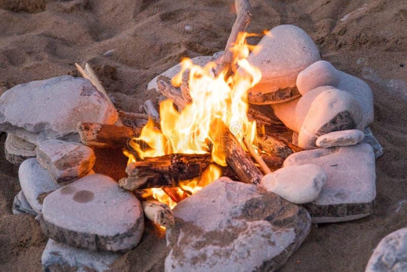 在岩石海滩篝火的阵营火 免版税库存图片
