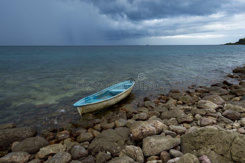 在岩石海滩的小船与雨风暴 免版税图库摄影